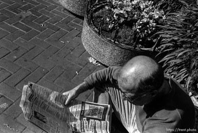 Man reading newspaper. Leica hip shots on the street.