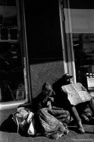 """Homeless couple with """"homeless and hungry"""" sign. Leica hip shots on the street."""