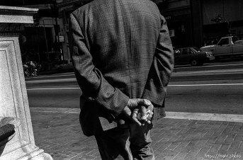 Man's back and hands. Leica hip shots on the street.