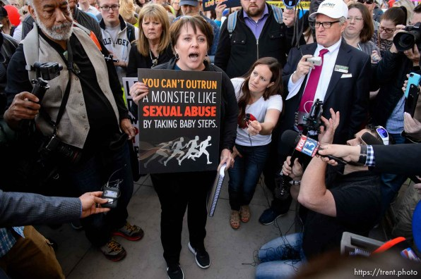 (Trent Nelson   The Salt Lake Tribune) People, including members of the Mormon Church, held a rally and marched to the LDS Church Office Building in Salt Lake City to request that the faith's leaders put an end to bishops meeting one-on-one with children for interviews. Friday March 30, 2018. Sue Krupa Gray makes a statement to two representatives of the LDS Church in front of the Church Office Building.