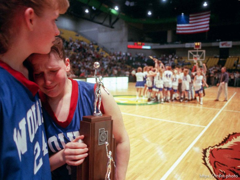 North Sevier basketball players Ann Braithwaite and Shadoe Shaheen (right) hold the second place trophy and grieve while the state champion Beaver Beavers celebrate their victory.
