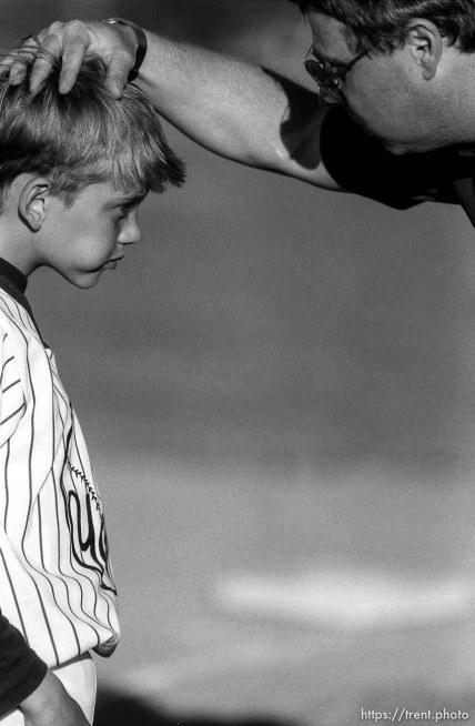 Coach talks to player at Yankees baseball game.