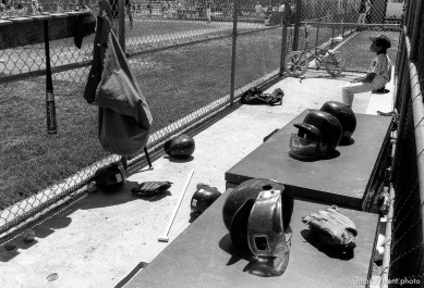 Kid in dugout full of gear at Yankee's game.