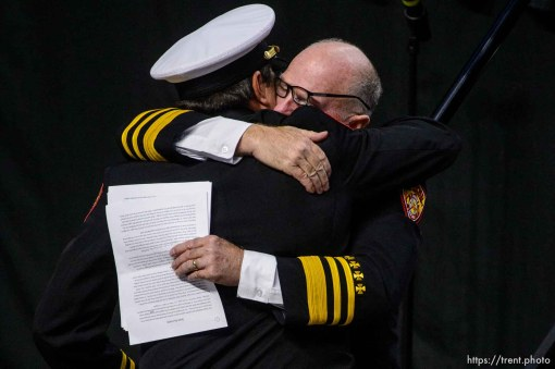 (Trent Nelson | The Salt Lake Tribune) Dominic Burchett (brother) is embraced by District Chief Duane Woolsey at the funeral services for Battalion Chief Matthew Burchett at the Maverik Center in West Valley City, Monday Aug. 20, 2018.