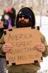 (Trent Nelson | The Salt Lake Tribune) A man holds a sign supporting Trump as protesters gather before a visit by President Donald Trump, Monday December 4, 2017.
