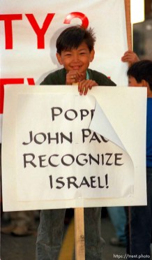 """kid with """"Pope John Paul Recognize Israel!"""" sign at the Pope's visit."""
