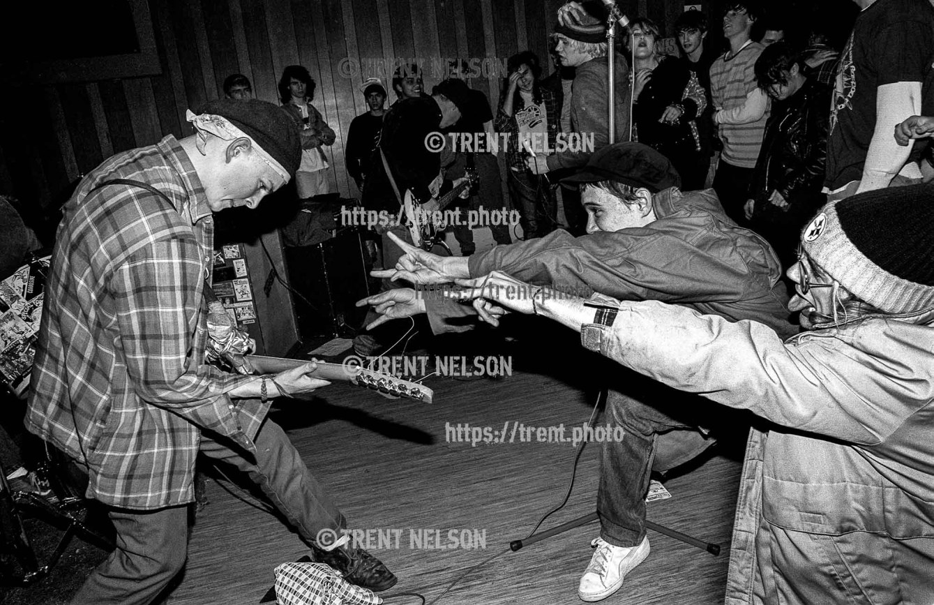 Operation Ivy fans jokingly taunt guitarist Tim Armstrong during a performance at the Veterans Hall in Davis, California, 1987.