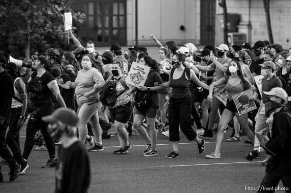 (Trent Nelson | The Salt Lake Tribune) Protesters link arms and walk toward a line of police in Salt Lake City on Thursday, July 9, 2020.