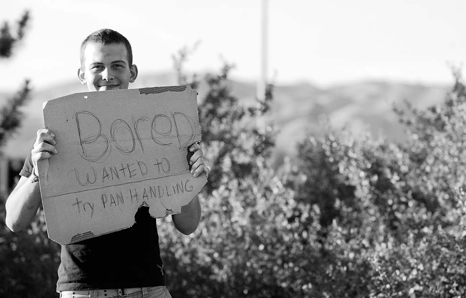 "Young man at a freeway exit, holding a sign reading, ""Bored, wanted to try panhandling.\"""