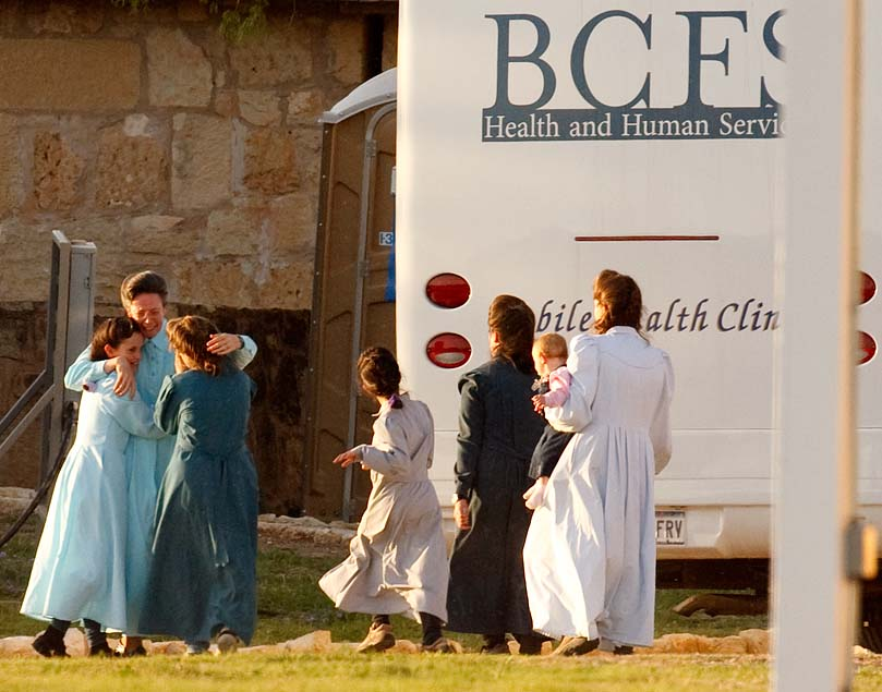San Angelo, Texas - Janet, an FLDS matriarch, tearfully embraces young girls as they arrive at the old historic Fort Concho, where nearly 500 FLDS women and children would be temporarily sheltered in primitive buildings such as former horse barns. The large amount of people that Texas Child Protective Services called victims overwhelmed the state's foster care system.