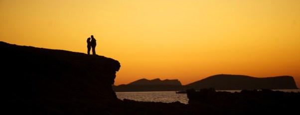 Pareja en el mar a la puesta de sol