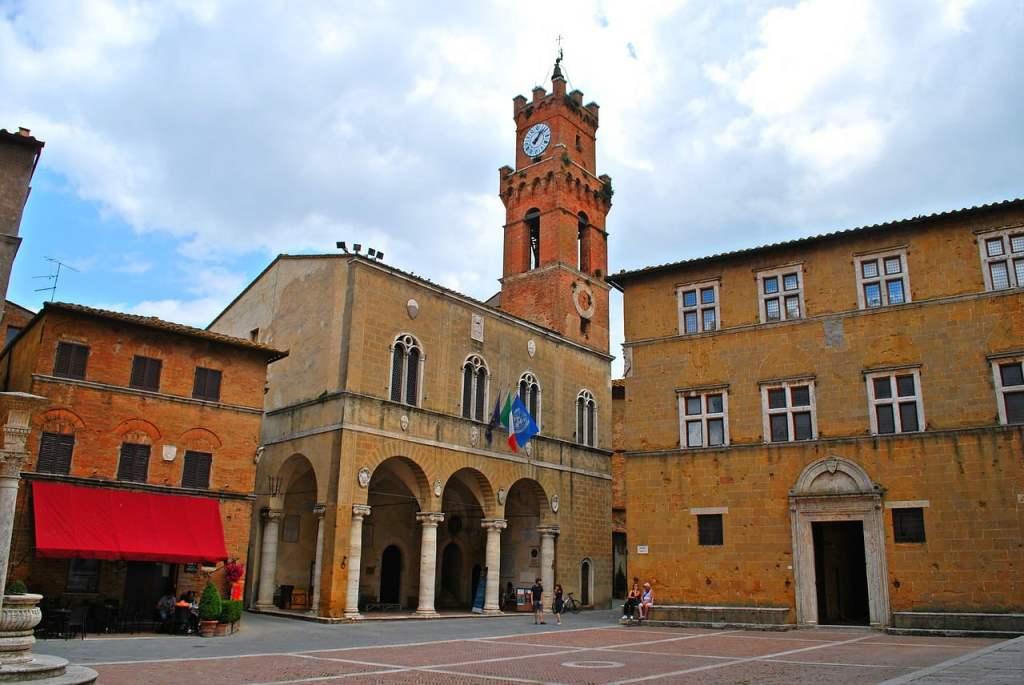 Piazza Pio II ha una forma armonica che dona regala solennità a tutti gli edifici circostanti, costruiti in pietra di travertino.