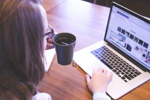 Woman sitting at a table drinking coffee in front of her laptop, working on her web presence