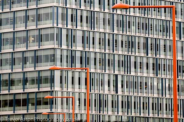Photograph of an office block and orange lampposts. photography photographer