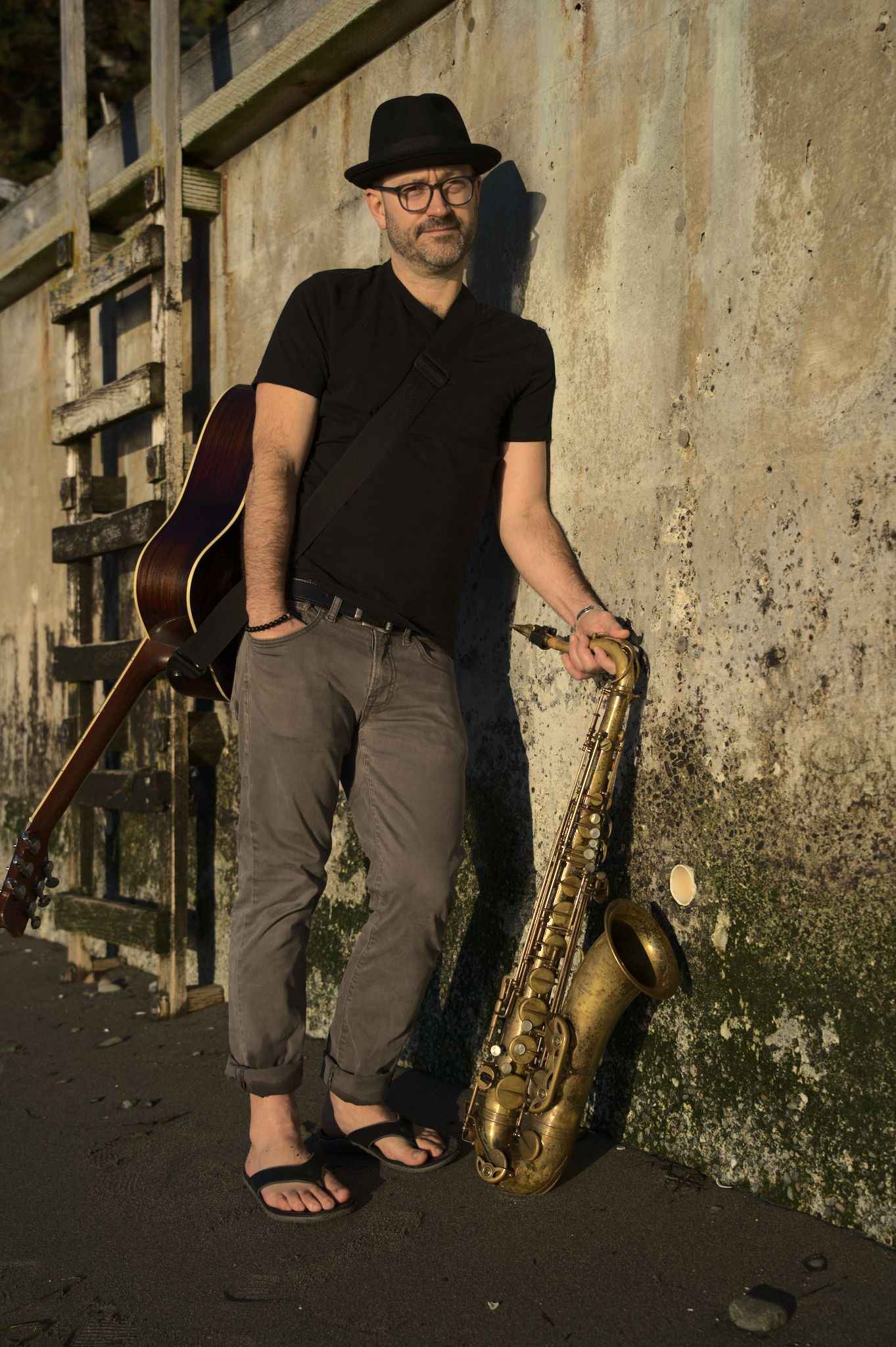 Trevor Ras with saxophone and guitar
