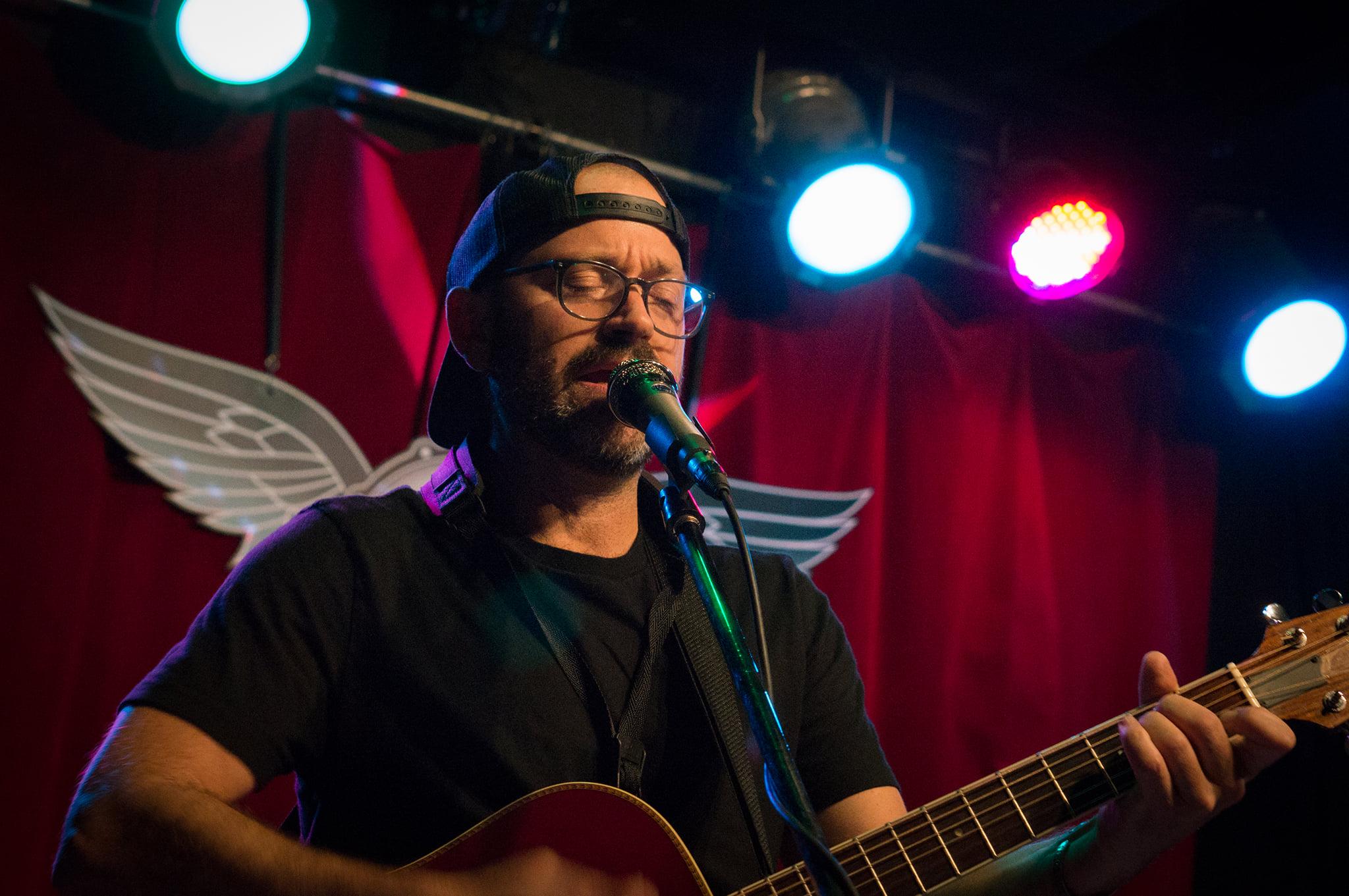Trevor Ras playing guitar at Skylark Cafe