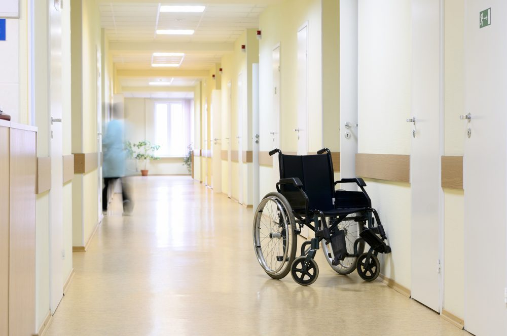 Wheel chair at the hospital corridor. Black wheel chair at the corridor of hospital.