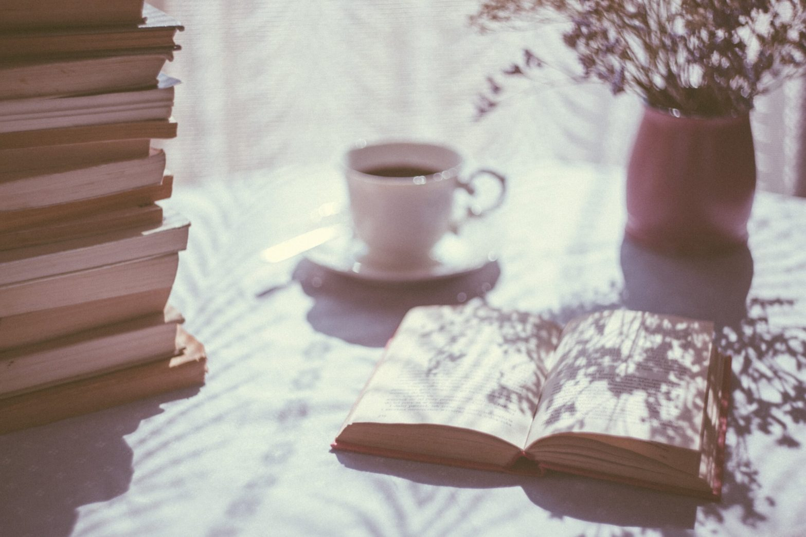 Book open on table with coffee behind it, stack of books to the left