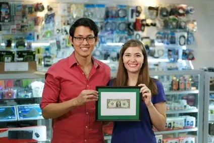 Image of owners of a small business holding a framed dollar bill