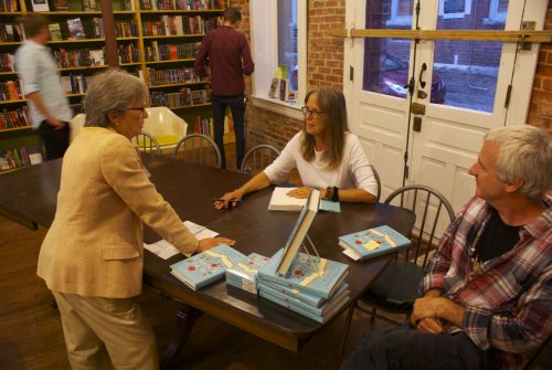 Woodroof talks to Councilwoman Nancy Hoffmann and bookstore owner Brian Lampkin after the reading.