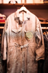 Denim pinstripe coveralls from the 1940s have hand-stitching on the pocket and pop burns on the lap.