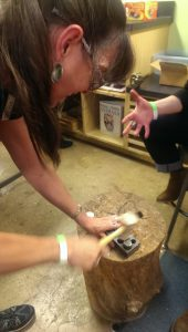 Women furiously pound down bottlecaps to make them into earrings. (Sayaka Matsuoka)
