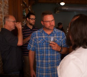 Fisher, center, and head brewer Scott Christoffel (left) at Natty Greene's downtown location
