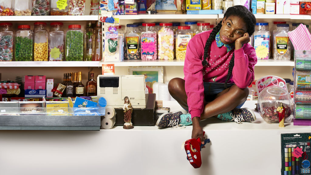 Michaela Coel as Tracy in Chewing Gum. Tracy is sitting cross-legged on a convenience store counter – there are rows of sweet jars lining the shelves behind her. Tracy looks into the camera with a bored expression, holding a pricing gun.