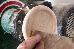 sanding wooden button on lathe