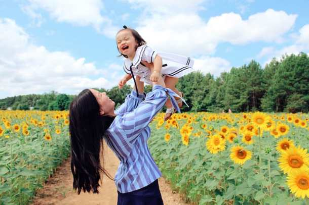 mother holding little girl in sunflower field in Dix Park in Raleigh