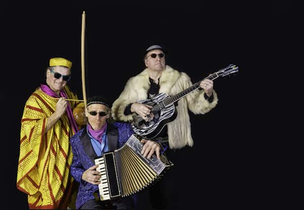 The three members of the band Craicdown, playing a guitar, accordion and a gourd