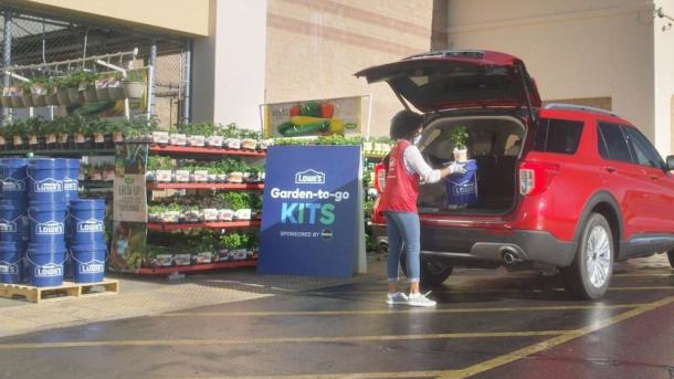 Lowe's employee putting plant in back of red car