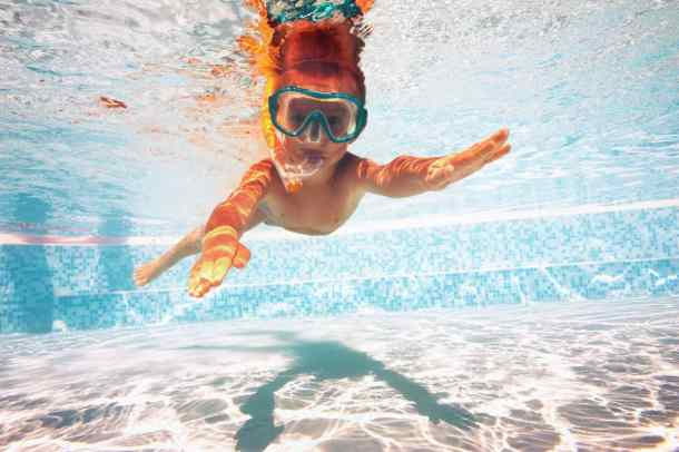 child swimming under water with mask