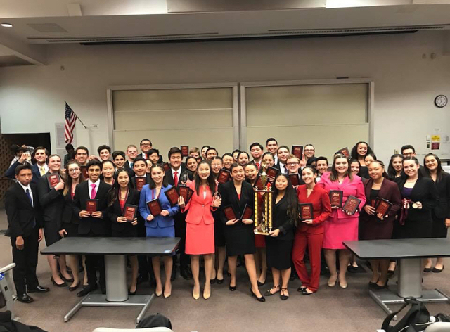 The+Speech+and+Debate+team+poses+with+their+first+place+trophy.+Photo+courtesy+of+Priscilla+Merit.