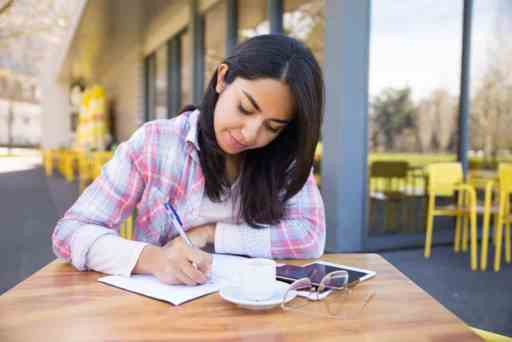 Focused young woman making notes in outdoor cafe. Pretty lady wearing casual clothes and sitting at table with chairs and building in background. Education concept. Front view.