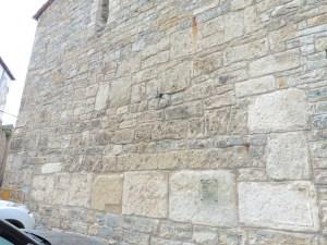 4. Carreus i inscripció reaprofitats a la part exterior de l'església. Fotografia: Servei d'Arqueologia i Paleontologia