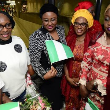 Aisha Buhari displays the Nigerian flag in a group photograph