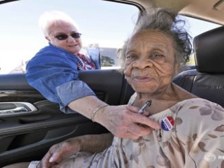 """Grace Bell Hardison, a 100-year-old woman recently mentioned by President Barack Obama after attempts were made to purge her from the voter registration list and hence deny her right to vote, receives an """"I Voted Today"""" sticker from election official Elaine Hudnell after she cast her ballot in the U.S. general election from a car in Belhaven, North Carolina. PHOTO: REUTERS."""