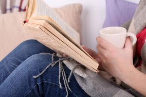 Woman sitting on sofa, reading book and drink coffee or tea, c