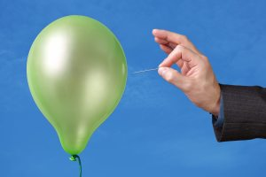 Needle about to pop a green balloon