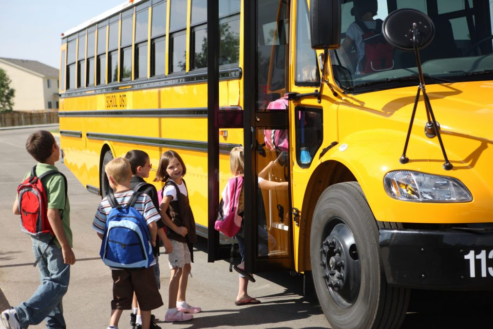Elementary school students get on school bus
