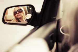 Blond fashion woman in sunglasses looking in the car mirror