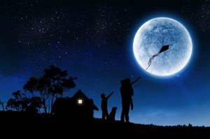 Silhouettes of happy family at night under full moon