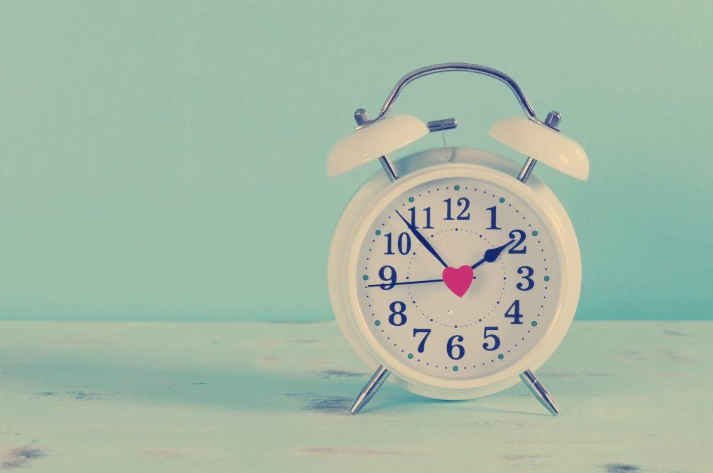 Retro Vintage Style Classic White Alarm Clock On Vintage Blue Ba