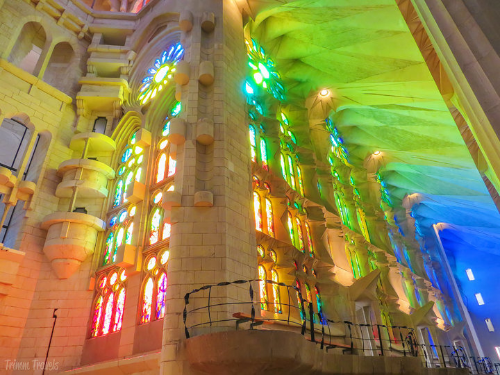 sun coming through the stained glass windows inside La Sagrada Familia in Barcelona Spain