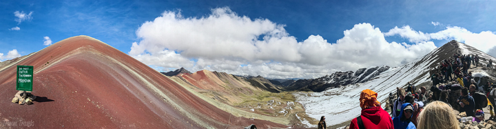 panoramic shot of Rainbow Mountain Peru and the snowy mountains across from it