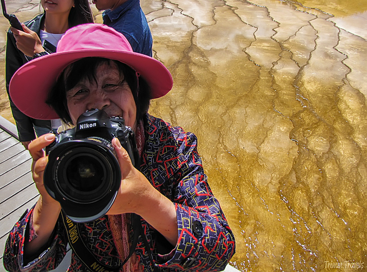 lady in a pink hat pointing her camera up at me in yellowstone