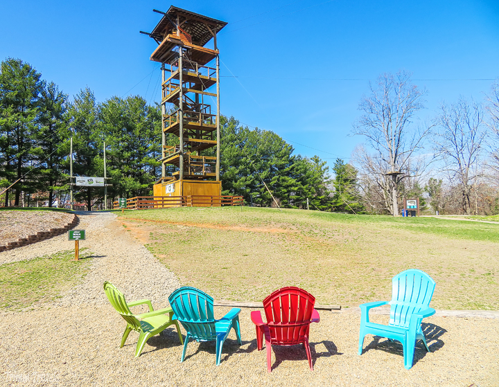 a view of a zipline tower and colorful adirondack chairs