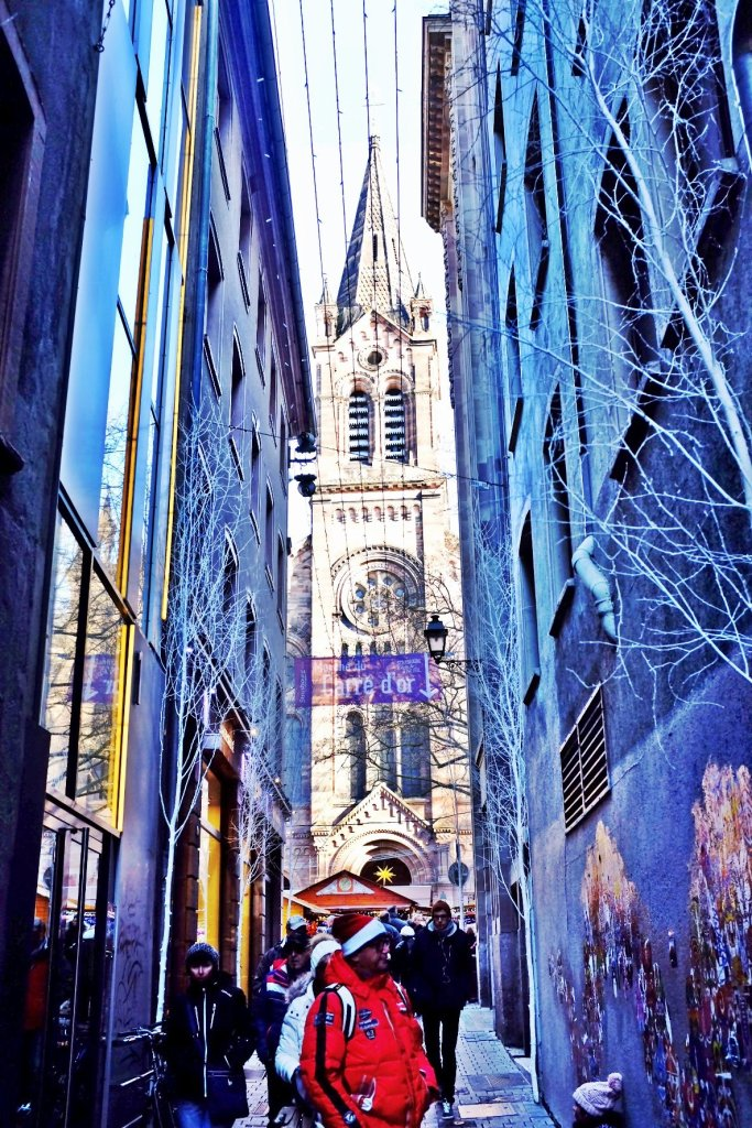 A church seen through a narrow alley in Strasbourg. Seen at the Christmas Markets