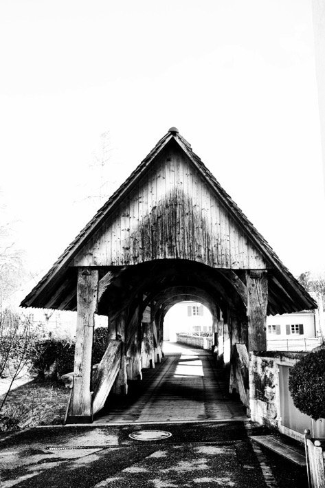 A black and white picture of the bridge that leads to castle Zwingen